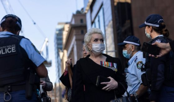 A protester stands near several police officers while speaking to the media during an anti-lockdown protest on Monday in Sydney.