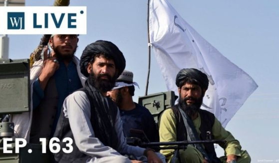 Taliban fighters stand on an armoured vehicle parade along a road to celebrate after the U.S. pulled all its troops out of Afghanistan, in Kandahar on Wednesday following the Taliban's military takeover of the country.