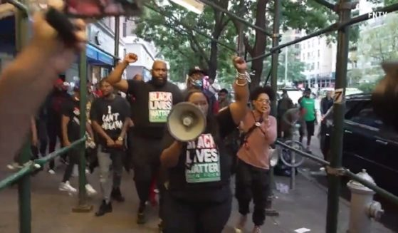 Black Lives Matter protesters demonstrate outside a New York City restaurant on Monday after a melee broke out last week between black diners and restaurant staff over proof of COVID-19 vaccination.