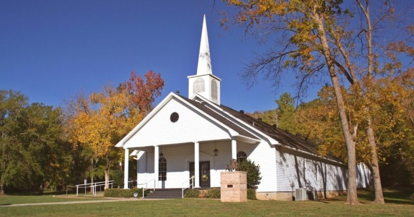 Small church in autumn with fall leaves and blue sky