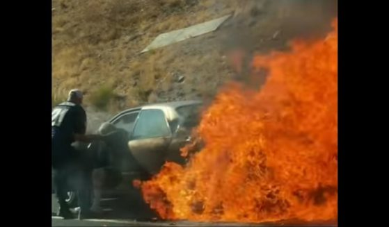 A good Samaritan pulls an elderly man from his burning car near San Digeo on Monday.