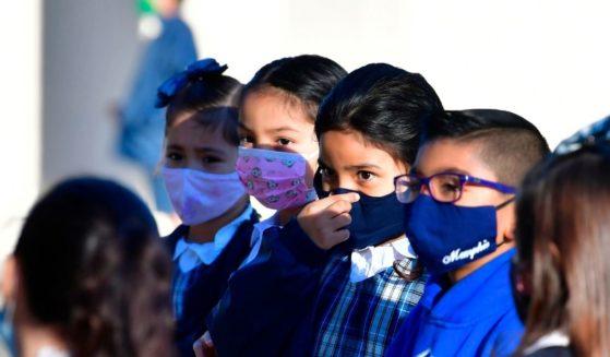 A student adjusts her mask at St. Joseph Catholic School in La Puente, California, on Nov. 16, 2020.