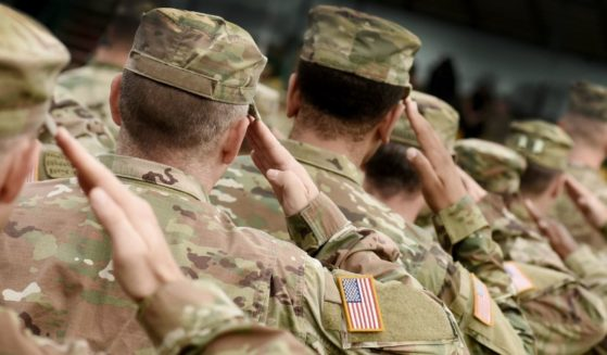 Soldiers salute in this stock image.