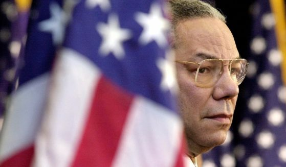 Colin Powell looks on as President George W. Bush addresses State Department employees in Washington on Feb. 15, 2001.