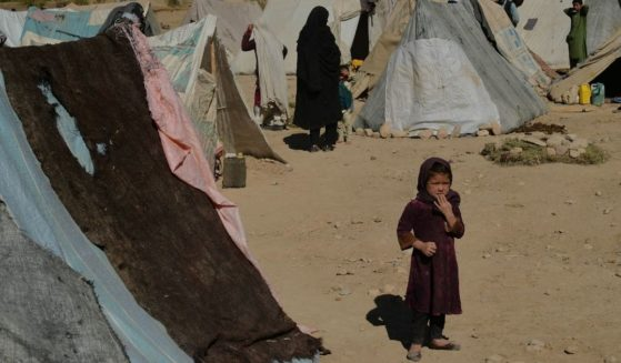 An Afghan girl stands next to tents at a temporary camp near a highway between Herat and Badghis on October 14, 2021. With winter coming on and most of the country plunged into abject poverty, some Afghan parents have resorted to the unthinkable: selling a child to survive.