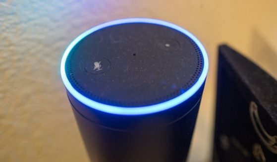 A close-up photo is taken of an Amazon Echo smart speaker and voice assistant with illuminated blue light ring, a device which uses the Amazon service to recognize and respond to users' voice commands, on May 7, 2018.