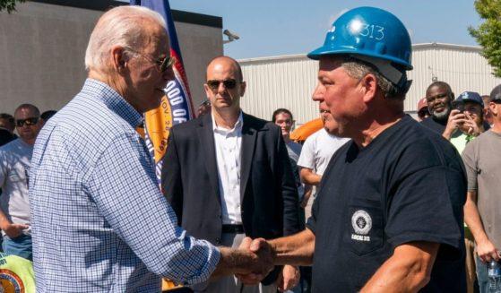 President Joe Biden, left, meets International Brotherhood of Electrical Workers union members in New Castle, Delaware on Sept. 6.