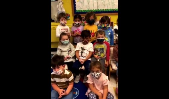 Young children are seen listening to a song about the importance of wearing masks.