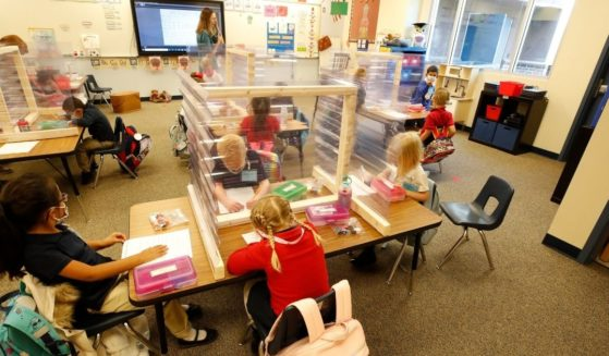 Throughout the coronavirus pandemic, young schoolchildren have been forced to wear masks and work behind shields, like these kindergarten students at Provo, Utah's Freedom Preparatory Academy in this photo from September 2020. Will their parents draw the line at vaccinating their 5- to 11-year-olds for COVID?