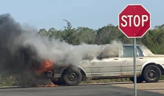 An old car belonging to Anna Hartman of Wichita, Kansas, is on fire at an intersection.