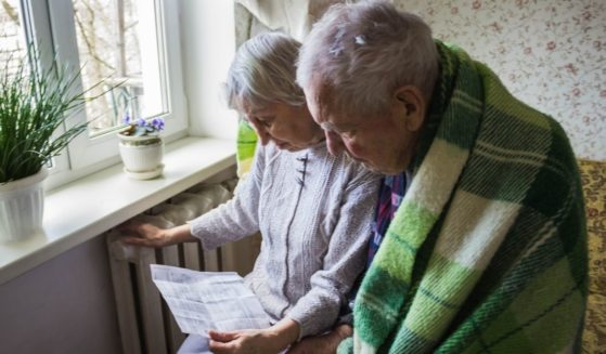 An elderly husband and wife look at their heating bill while sitting in front of a radiator for warmth.