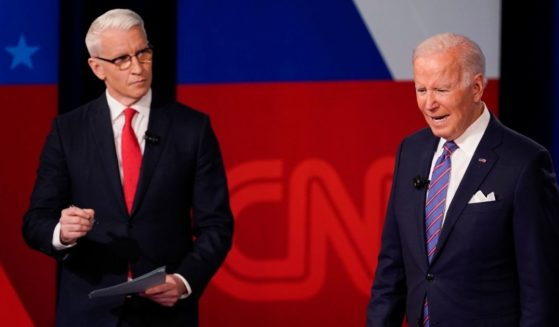 CNN's Anderson Cooper, left, had to prompt a confused-looking President Joe Biden as Biden responded to questions during Thursday's televised town hall event.
