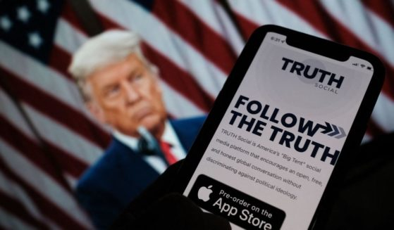 A person checks the app store on a smartphone with a photo of former President Donald Trump in the background in Los Angeles on Wednesday.