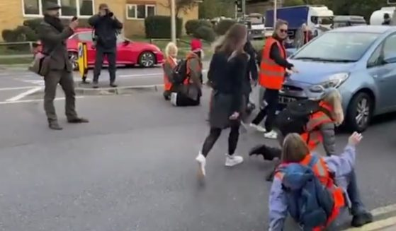 Environmental protesters in London are dragged off the street by frustrated drivers.