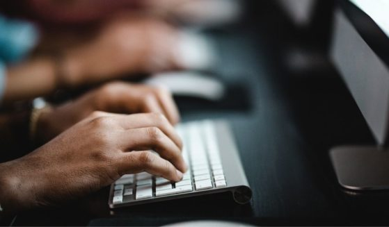 """This stock image portrays workers typing on computer keyboards. Federal investigators are reportedly issuing """"keyword warrants"""" to Google to examine internet users' search histories."""