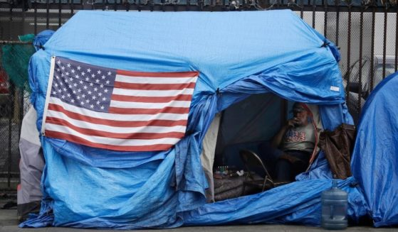 A man smokes inside a tent on skid row in Los Angeles in this file photo from March 2020. The Secretary for the U.S. Department of Veterans Affairs has pledged to move quickly to house Los Angeles-area homeless veterans.