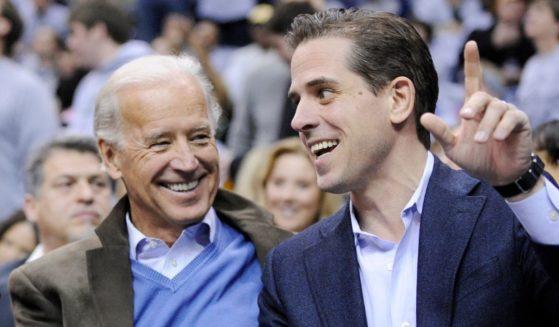 Then-Vice President Joe Biden, left, and his son Hunter Biden talk at the Duke Georgetown NCAA college basketball game on Jan. 30, 2010, in Washington.