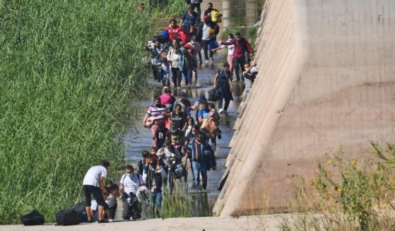 Migrants illegally cross the border from Mexico into San Luis, Arizona on Sunday.