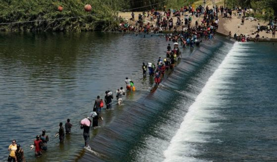 Haitian migrants cross into the United States in large numbers, using a dam in the river near Del Rio, Texas on Sept. 18.