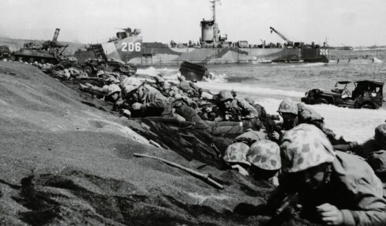 United States Fourth Division Marines take cover from enemy fire on the shores of Iwo Jima during World War II in Japan on Feb. 19, 1945.