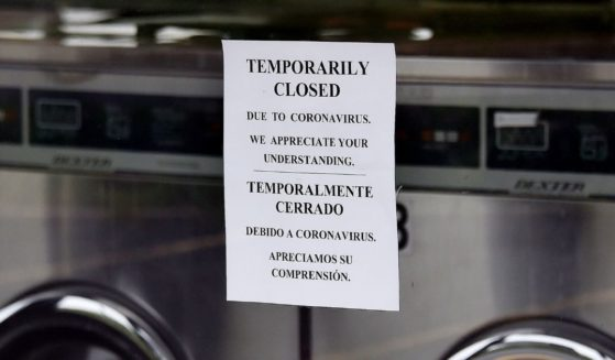 A laundromat window displays a sign explaining its status as temporarily closed as more businesses make the decision to reopen amid the coronavirus pandemic on May 18, 2020, in Arlington, Virginia.