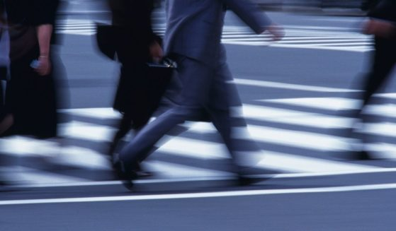 People walk across a street in the above stock image.