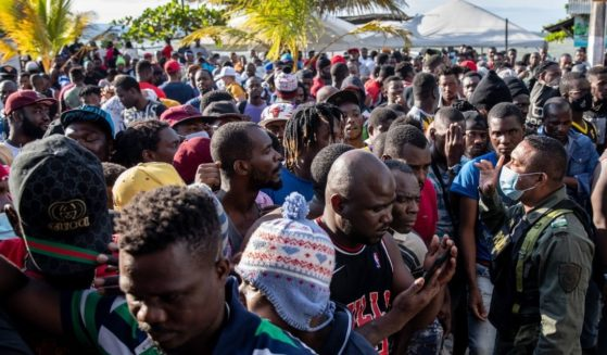 Haitian immigrants wait after Colombian police temporarily closed a ferry boat ticket office because of crowd control issues in Necocli, Colombia, on Monday.