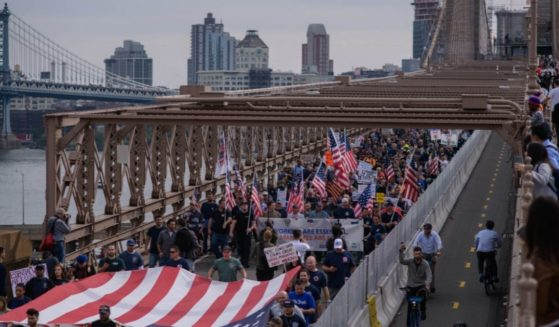 Thousands of New York City municipal workers marched across Brooklyn Bridge during a Monday protest against the city's COVID-19 vaccine mandate.