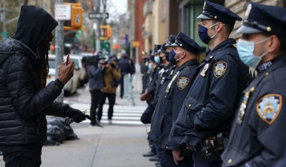 A protester confronts New York Police Department officers outside Washington Square Park in New York on April 12.