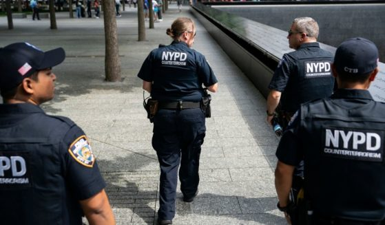 A group of NYPD officers patrols along the south reflecting pool at the 9/11 Memorial and Museum on Aug. 16, 2021.