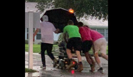 Four good Samaritans push an elderly woman in a scooter