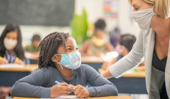 A masked teacher interacts with a masked student in this undated stock photo image. A Florida school district has come under fire for failing to advise parents of a special-needs student that they were tying a mask to the child's face every day.