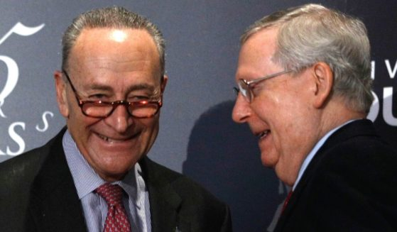 Then-Senate Majority Leader Mitch McConnell, right, and Minority Leader Chuck Schumer shake hands after Schumer spoke at the University of Louisville's McConnell Center in Louisville, Kentucky, on Feb. 12, 2018.