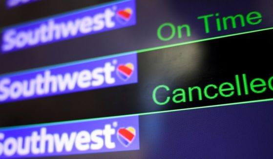 A screen displays Southwest Airlines flight information at Baltimore Washington International Thurgood Marshall Airport on Monday. Southwest Airlines cancelled hundreds of flights over the weekend, blaming air traffic control issues and weather. An airline representative denied reports that the problems are in reality due to pilots calling in sick to protest COVID-19 vaccination mandates.