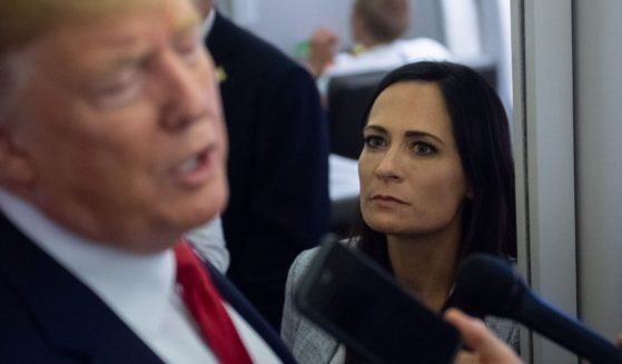 Then-White House press secretary Stephanie Grisham listens as President Donald Trump speaks to the media aboard Air Force One while flying from El Paso, Texas, to Joint Base Andrews in Maryland on Aug. 7, 2019.