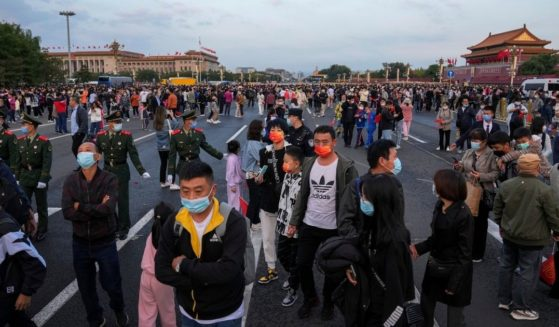 Thousands of people disperse after gathering in Tiananmen Square for a flag raising ceremony on Friday.