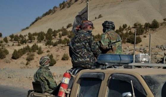 Taliban fighters travel on a pick-up truck along a road in Band Sabzak area in Badghis, Afghanistan, on Sunday.