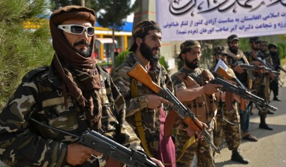 Taliban fighters stand guard near the venue of an open-air rally in a field on the outskirts of Kabul on Oct. 3.