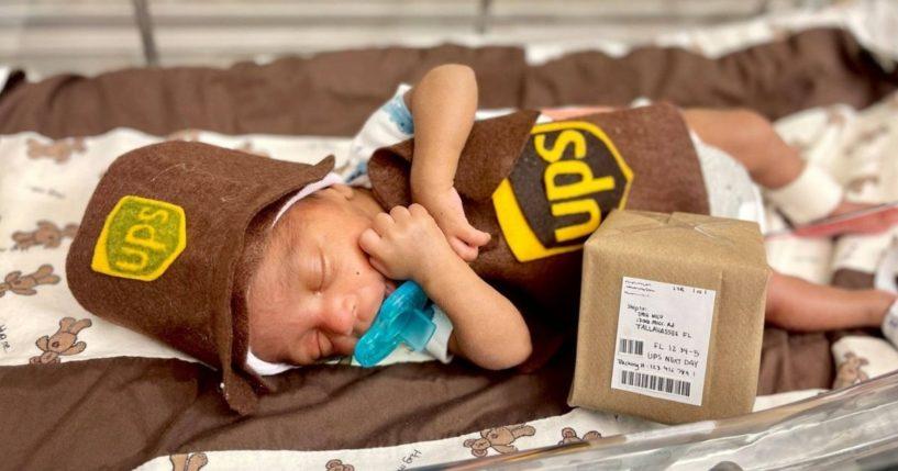 A NICU baby dressed in a UPS costume