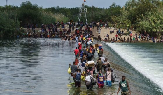 Migrants, many of them Haitian, cross the Rio Grande to get food and supplies near the Del Rio-Acuna Port of Entry in Ciudad Acuna, Coahuila state, Mexico on Sept. 18.