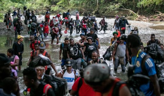 Migrants, most from Haiti, ford one of many rivers they will cross while on a trek through the infamous Darien Gap on their journey towards the United States on October 07, near Acandi, Colombia.