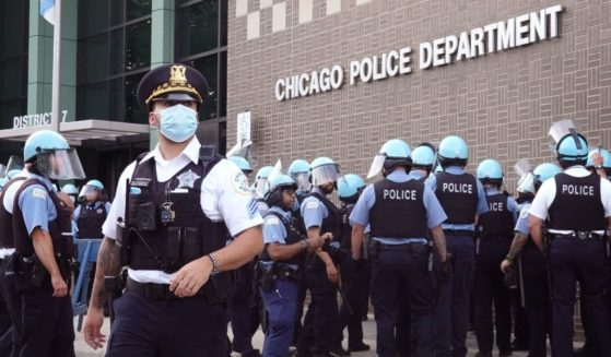 Chicago police stand guard as demonstrators protest outside the department's 7th District station on Aug. 11, 2020.