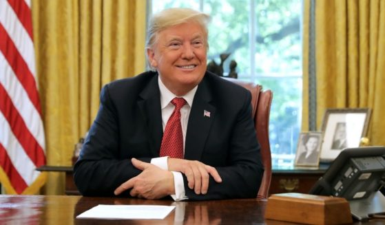 Then-President Donald Trump talks to reporters while hosting workers and members of his Cabinet for a meeting in the Oval Office at the White House on Oct. 17, 2018.