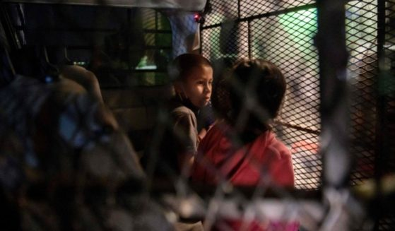 Two unaccompanied children who illegally crossed the Rio Grande from Mexico stand at a makeshift processing checkpoint before being detained by Border Patrol agents in Roma, Texas, on March 27.
