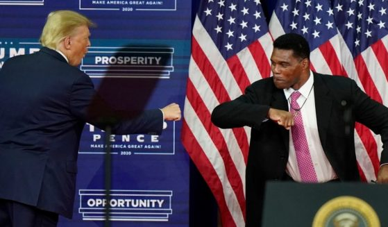 Former NFL great Herschel Walker bumps elbows with then-President Donald Trump in a September 2020 file photo from the presidential campaign in Atlanta.