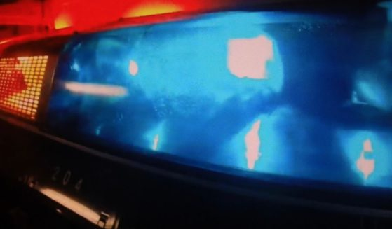 A stock photo shows sirens flashing on top of a police car.