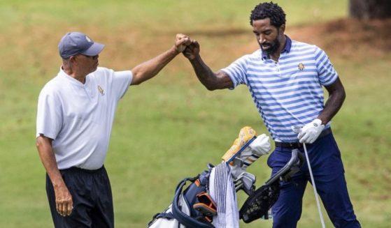 Head golf coach Richard Watkins stands with J.R. Smith at the Phoenix Invitational Golf Tournament in Burlington, North Carolina, on Tuesday.