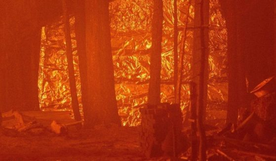 A structure is wrapped in foil to protect it from flames as a neighboring structure burns during the Caldor Fire near South Lake Tahoe, California, on Aug. 29, 2021.