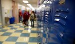 Stock photo of a high school hallway with a group of students at the far end.