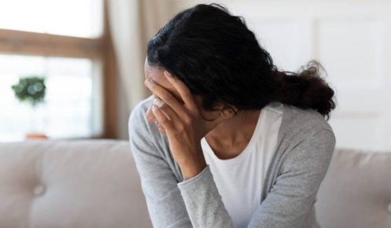 A stock photo shows a woman sitting with her face in her hand, looking sad.